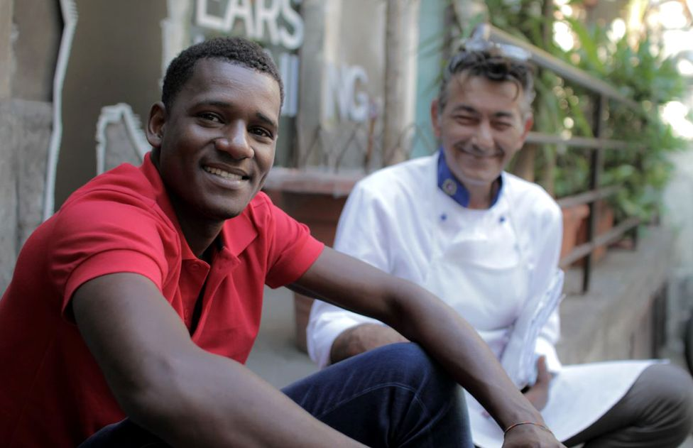 Yahya and Salvo Baltico sit outside 11Eleven restaurant in Sicily