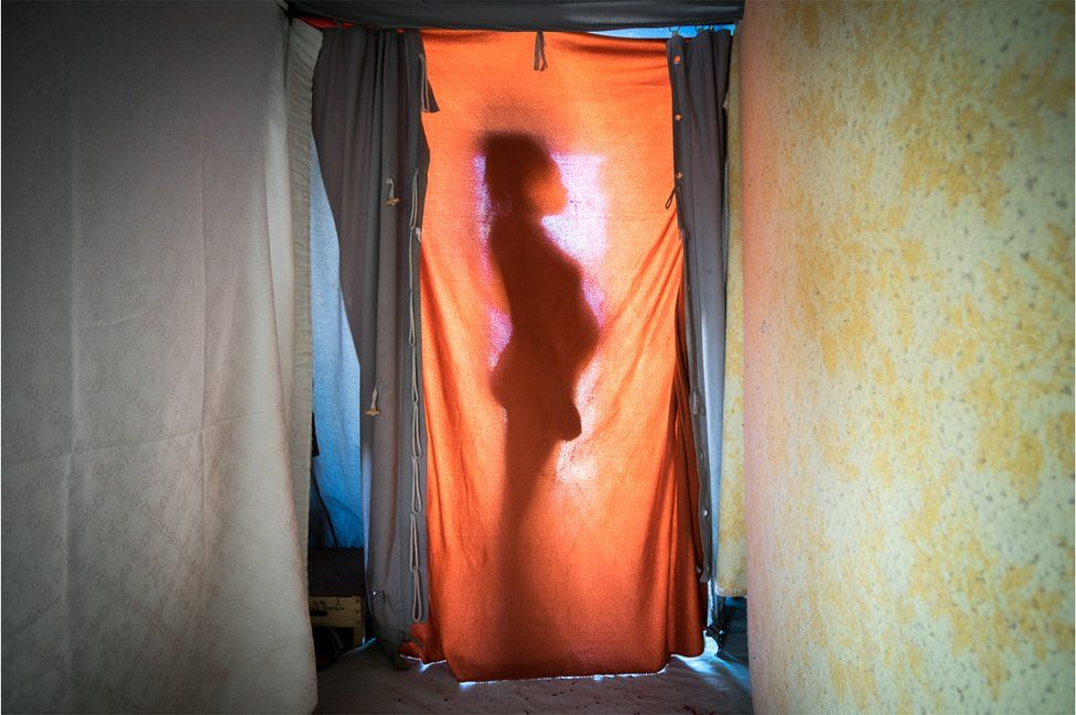 Mohamed Fatima is silhouetted against a sheet