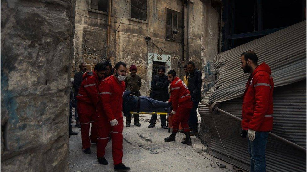 Stretcher being carried through street in eastern Aleppo by Red Crescent and Red Cross doctors, Wednesday 7 December 2016