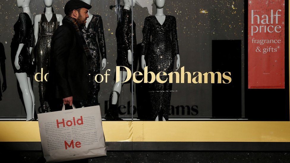 Man walking in front of Debenhams window