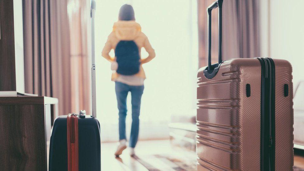 Woman who has just entered hotel room with suitcases
