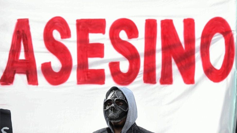 "A man with a mask stands before a placard reading ""murderer"""