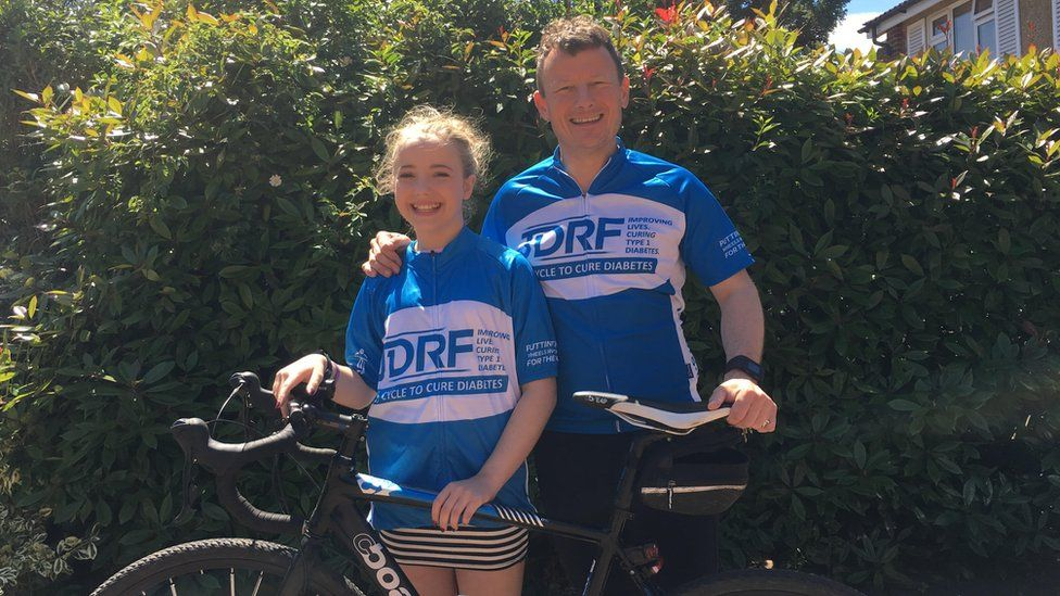 Jason Wills (right) with his daughter, Maddie (left), standing with the bike that was stolen
