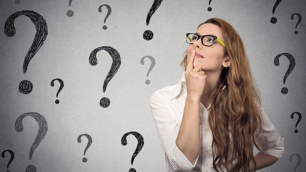 Woman looking at question marks