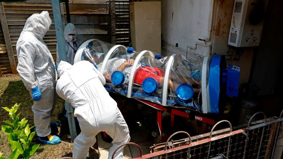City of Tshwane's Special Infection Unit paramedics and a doctor load a man showing symptoms of COVID-19 coronavirus into the isolation chamber equipped with a negative pressure filtration system from his home in the north of Pretoria, South Africa, on January 15, 2021.