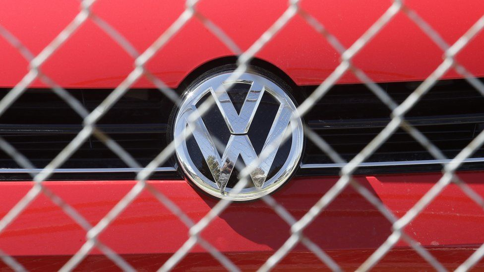 A Volkswagen diesel sits behind a security fence