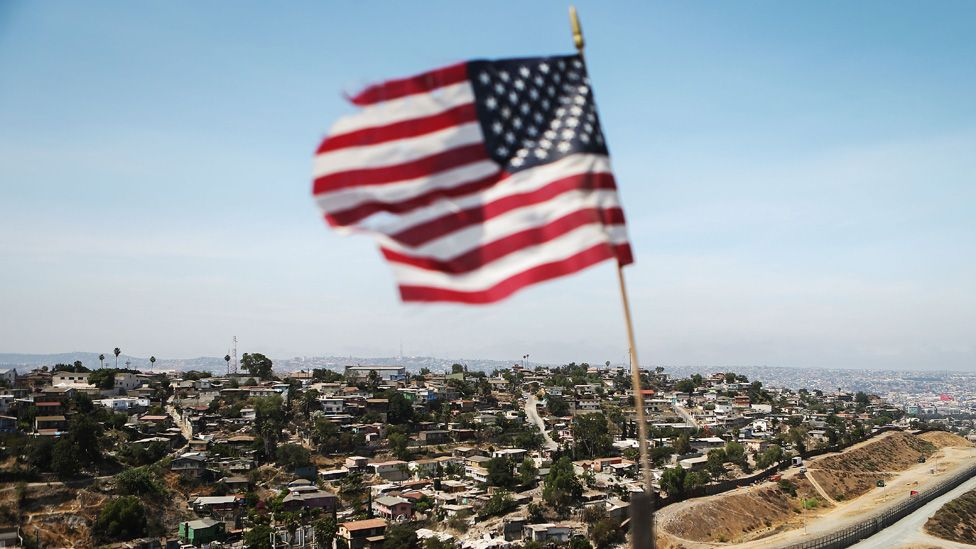 A flag flies over the US-Mexico border