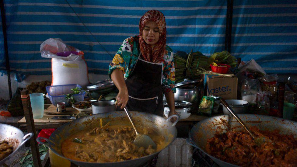 Menyw yn coginio Ayam Rendang yn Malaysia
