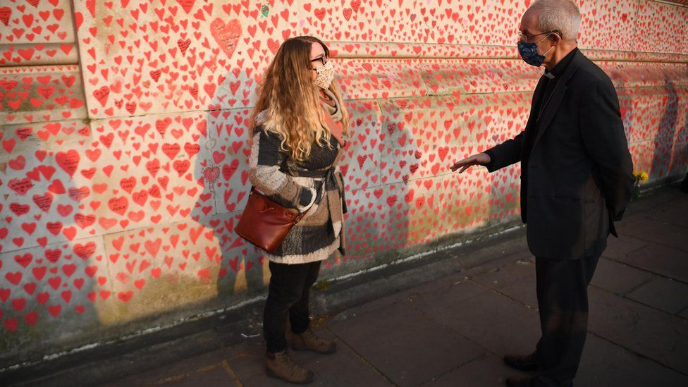 Jo Goodman speaking to the Archbishop of Canterbury next to the National Covid Memorial Wall in London