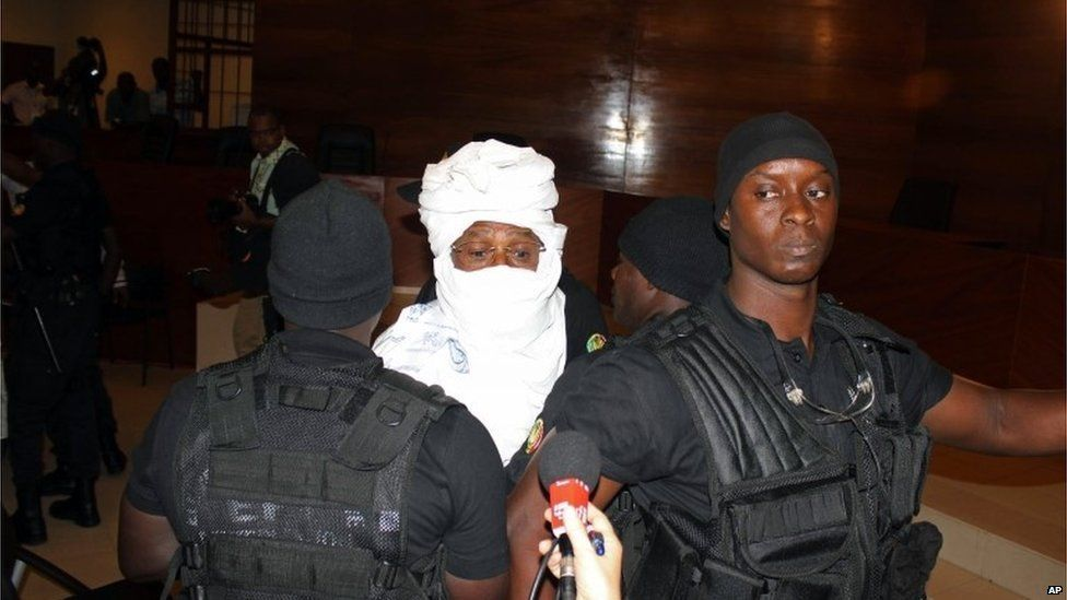 Security personnel surround former Chadian dictator Hissene Habre inside the court in Dakar, Senegal, Monday, July 20, 2015