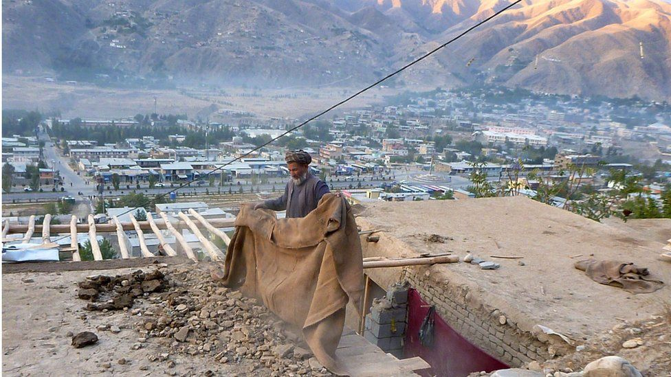 An Afghan repairs his roof damaged in an earthquake, in Badakhshan, Afghanistan (26 October 2015)
