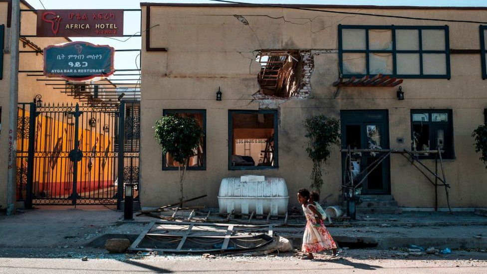 Children play in front of a hotel damaged by mortar shelling, in Humera, Ethiopia, on November 22, 2020.