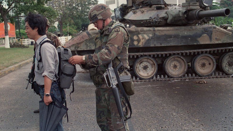 A US soldier searches the bag of a Papal courier during Operation Just Cause, outside the Vatican embassy in Panama City on 28 December, 1989.