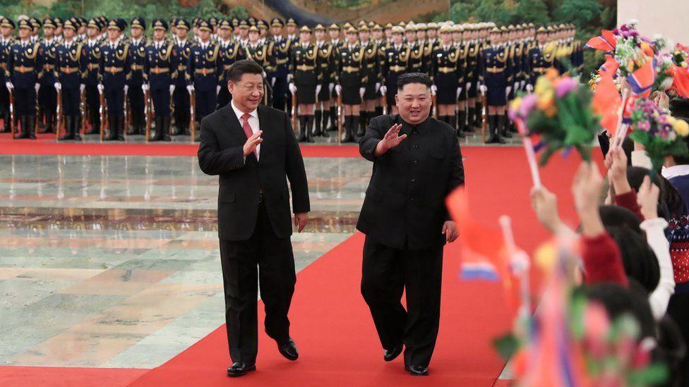 "North Korean leader Kim Jong Un (R) and China""s President Xi Jinping waving to children"