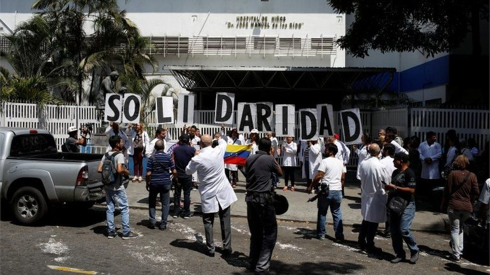 """Venezuelans, including doctors, hold banners that read """"Solidarity"""" as they gather outside a public children hospital during an ongoing blackout in Caracas, Venezuela March 10, 2019."""