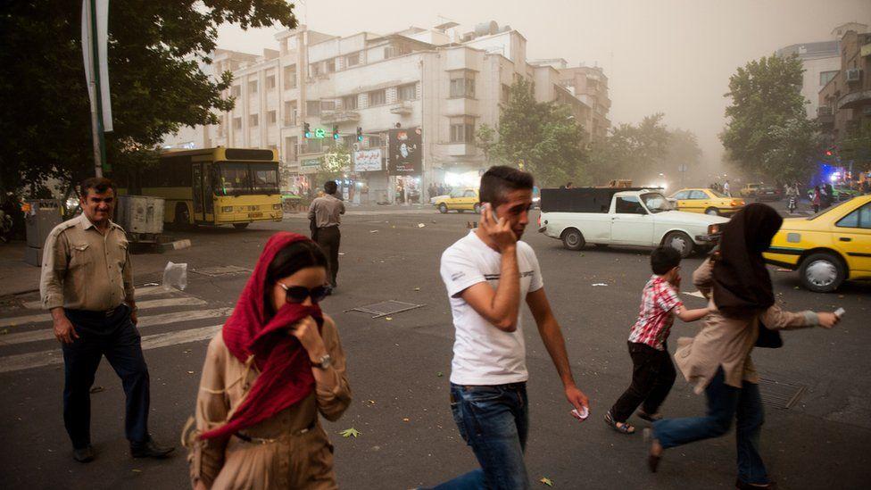 Iranians walk amid a sand storm in Tehran (2 June 2014)