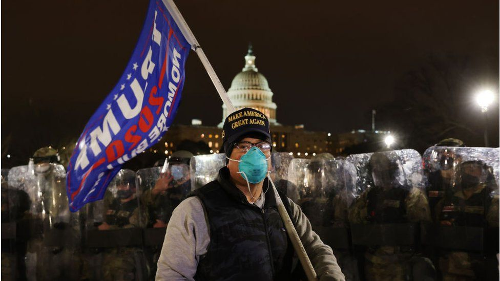 A man in a Trump hat holds a Trump flag outside the US Capitol hours after a riot was declared
