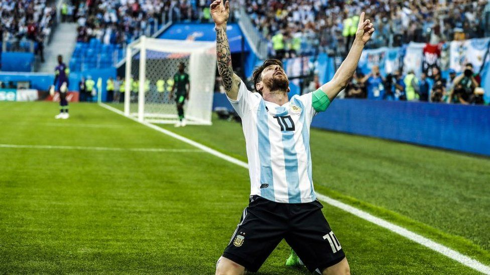 Lionel Messi kneeling looks at the sky.