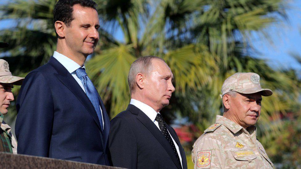 Syrian President Bashar al-Assad (L), Russian President Vladimir Putin (C), Russian Defence Minister Sergei Shoigu (R) visit the Hmeimim airbase in Syria (11 December 2017)