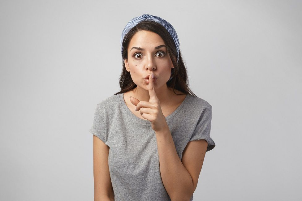 Woman with finger on lip asking for silence