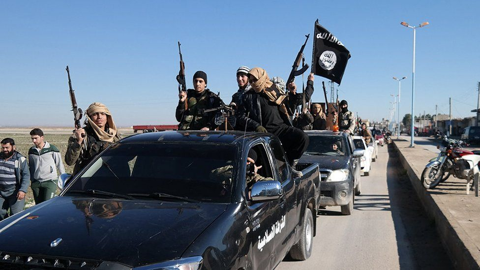 Photo released in May 2015, by a militant website, showing Islamic State militants pass by a convoy in northern Syria