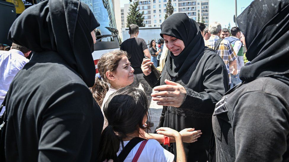 In this file photo taken on August 06, 2019, family and friends say goodbye as Syrian refugee voluntarily board buses returning to neighbouring Syria in the Esenyurt district of Istanbul