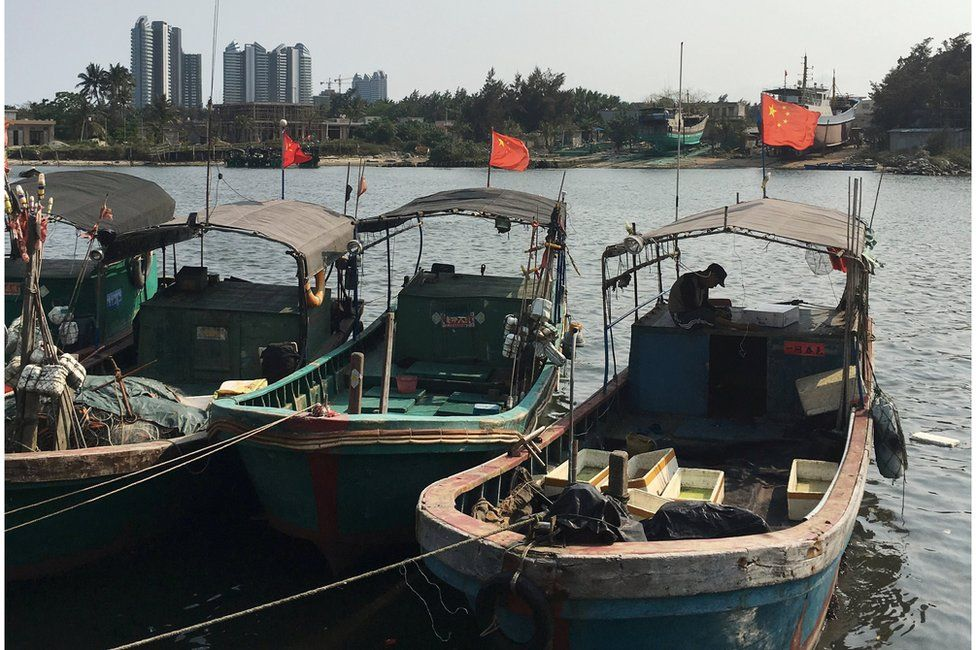 Fishing boats flying red flags in a harbour in Baimajing, Hainan province, 7 April 2016.