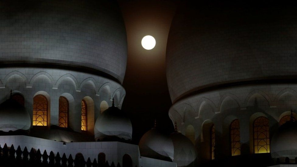 rises behind the Sheikh Zayed Grand Mosque in Abu Dhabi