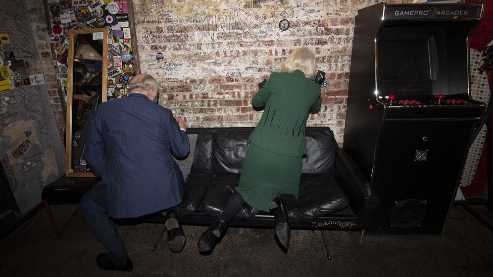 Charles and Camilla signing the 100 Club wall