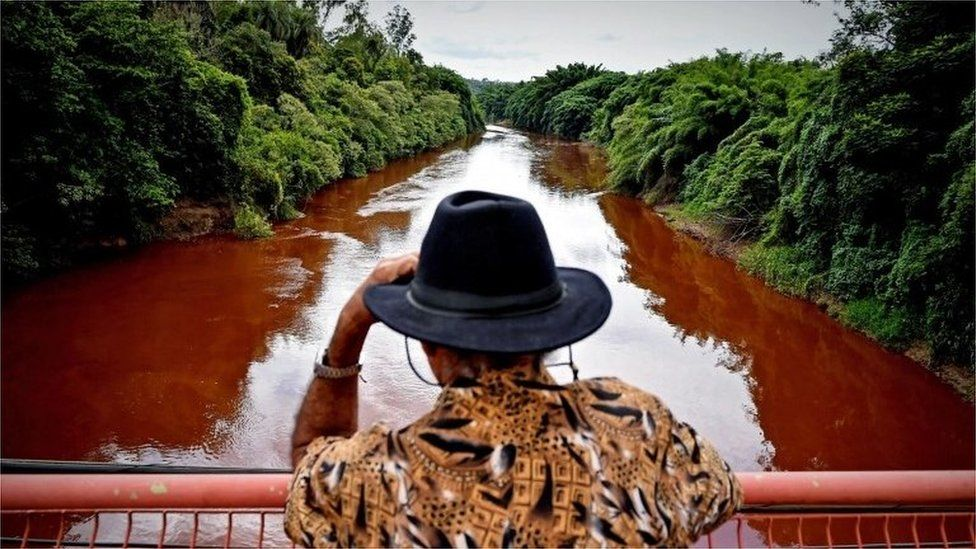 A man watches the Paraopeba River with mud and waste from the disaster caused by dam spill in Brumadinho, Minas Gerais, Brazil, 26 January 2019.