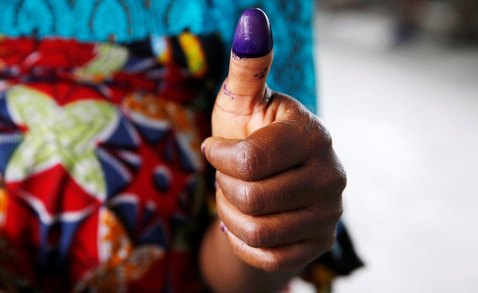 Woman showing her inked thumb