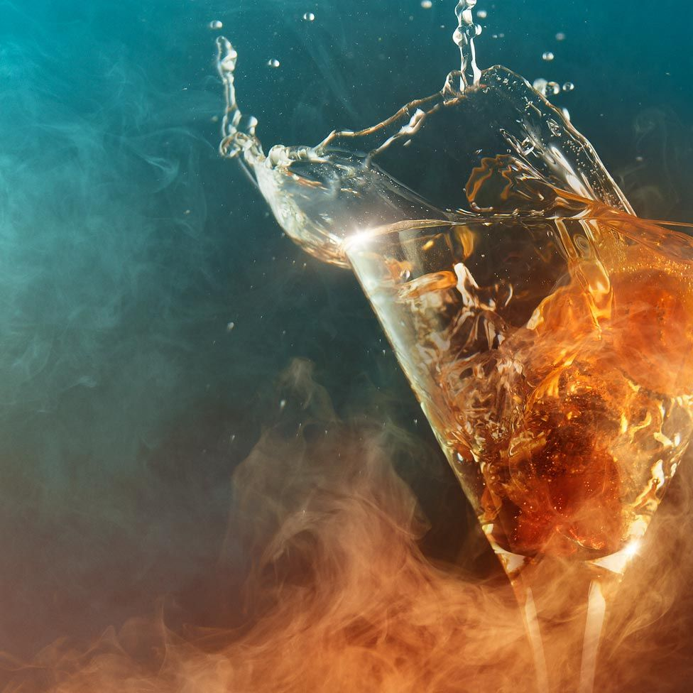A glass with the drink splashing out