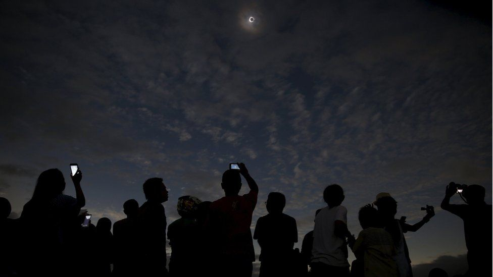 People taking pictures of the eclipse with their phones, on Ternate island, Indonesia