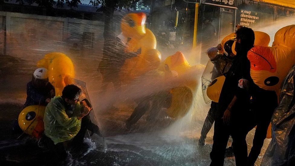 Demonstrators use inflatable rubber ducks as shields to protect themselves from water cannons during an anti-government protest in Bangkok, Thailand, November 17, 2020