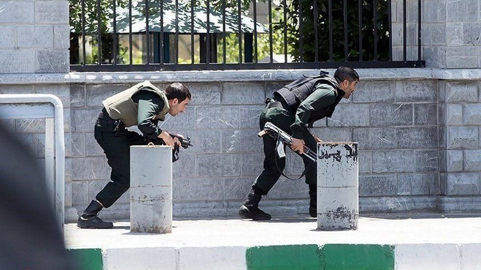 Members of Iranian forces take cover during an attack on the Iranian parliament in central Tehran, Iran, June 7, 2017