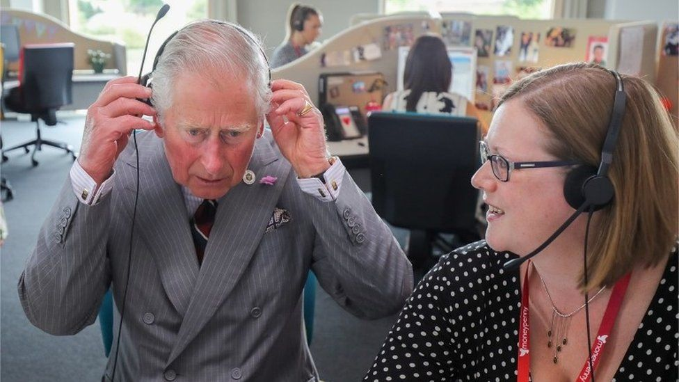 Prince Charles listens in to a telephone call during a visit to Moneypenny Ltd