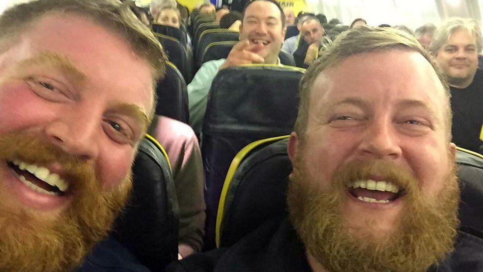 Two men who look very similar taken on a plane
