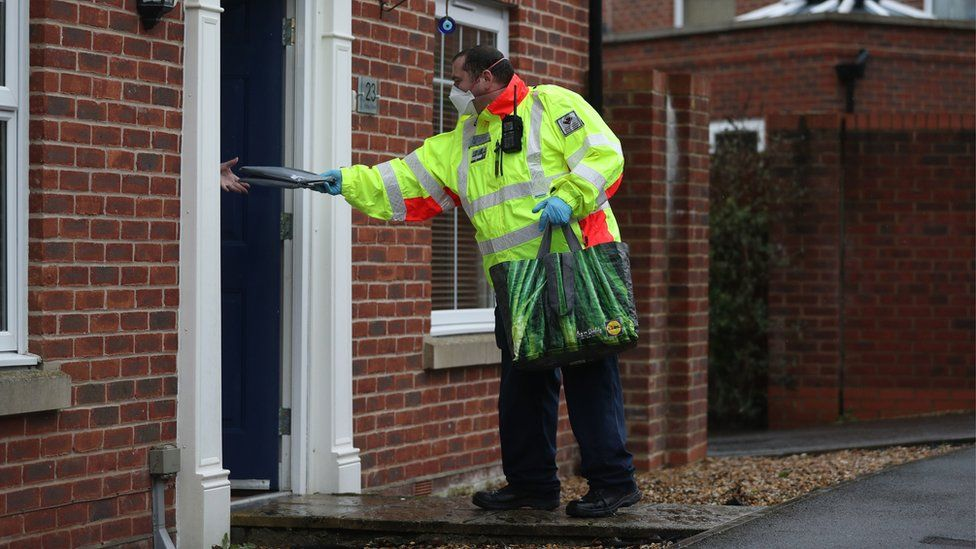 A Community safety patrol officer hands a coronavirus test to a resident in Bramley Green, Hampshire, during a surge testing programme after a case of the South African variant of Covid-19 was identified in the village