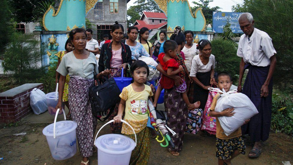 Rakhine ethnics who fled from fighting area carry their belongings as they arrive to take refuge at a monastery in Boothee Taung town, Rakhine State, western Myanmar, 13 October 2016.