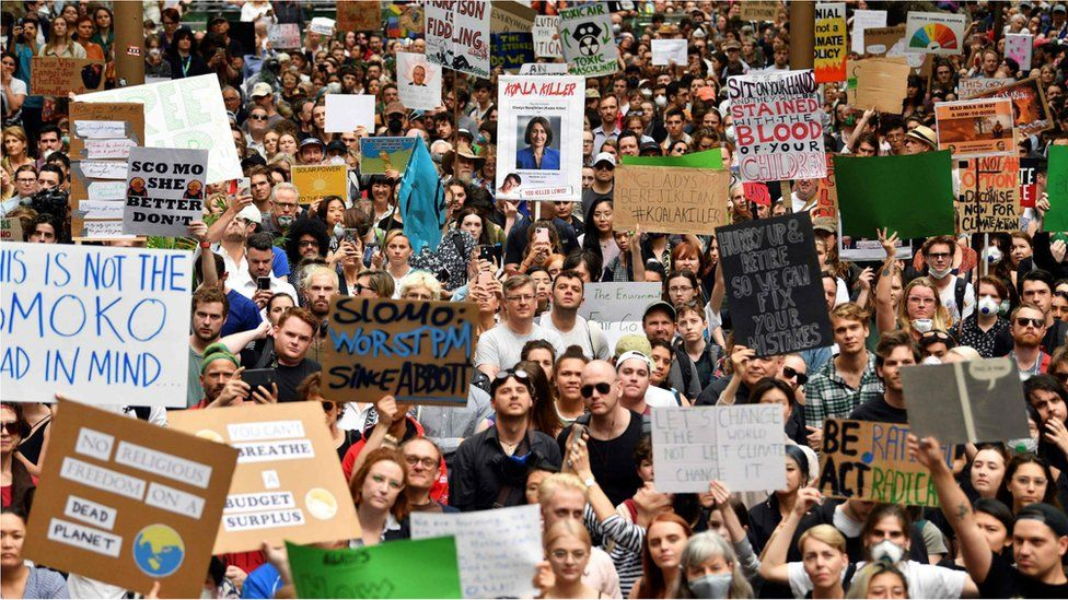 Demonstrators hold up placards at a climate protest rally in Sydney on 11 December, 2019