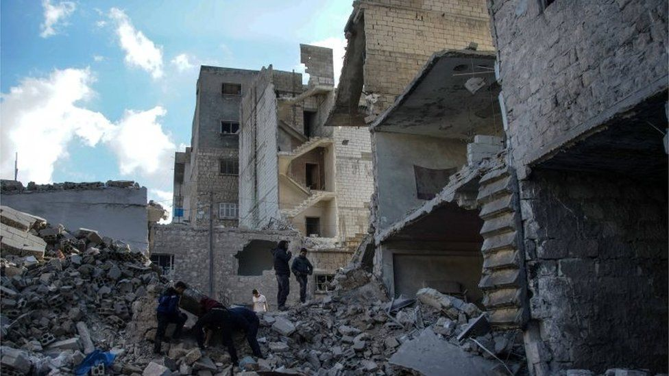 People inspect the rubble after airstrikes, at a marketplace in Areeha town (Jericho town), southern Idlib,