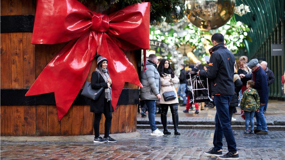 Woman posing next to Christmas decorations in London's Covent Garden