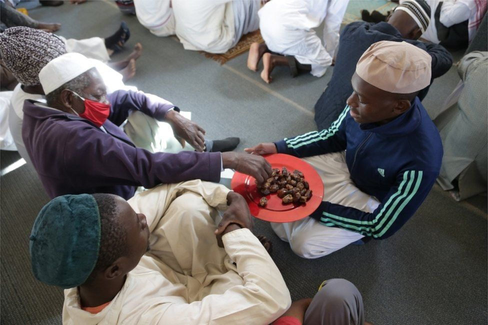 A man hands out dates to worshippers.