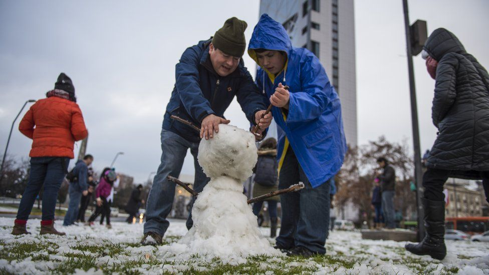 People make a snowman in Santiago on July 15, 2017