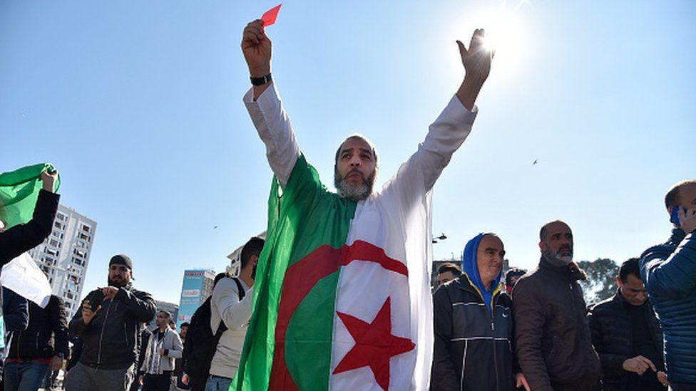 An Algerian protestor wears the national flag at a protest in Algiers