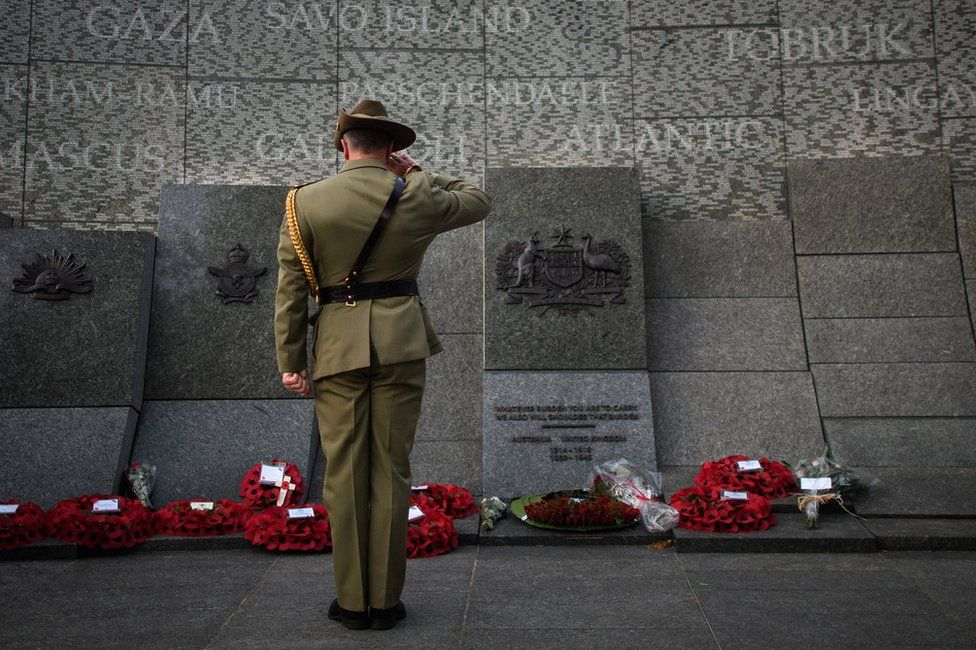A soldier salutes after laying a wreath on the Australian War Memorial at Hyde Park Corner