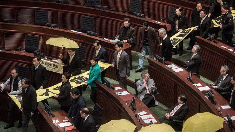 Pro-democracy lawmakers walk out in protest before the policy address of Hong Kong Chief Executive Leung Chun-ying in the legislative council in Hong Kong on January 14, 2015