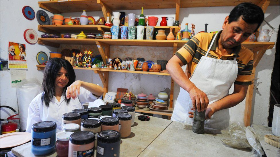 An Afghan refugee works on a pot in the pottery workshop of the Citta' Futura Project on June 22, 2011 in Riace.