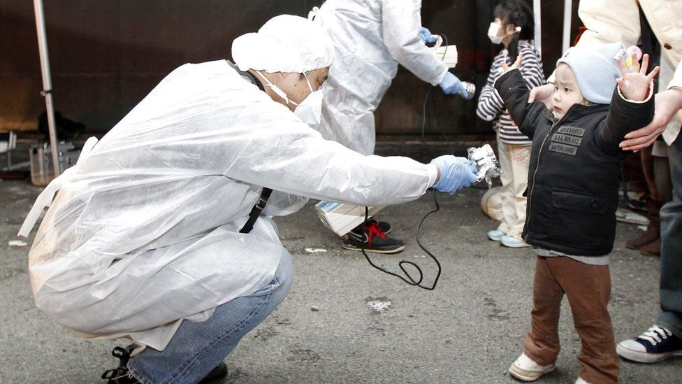 A child being screened for radiation following the Fukushima nuclear disaster