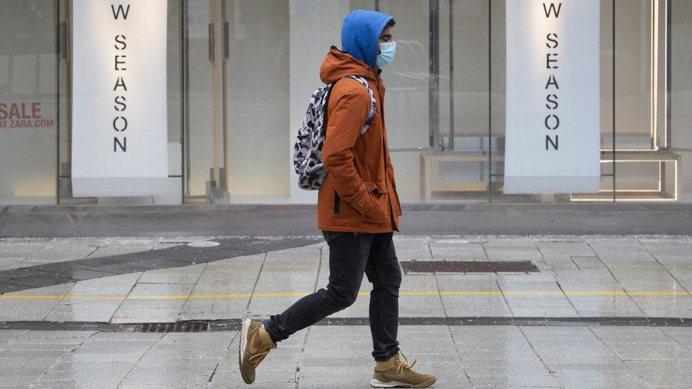 A man wearing a face mask walks in Cardiff, Wales